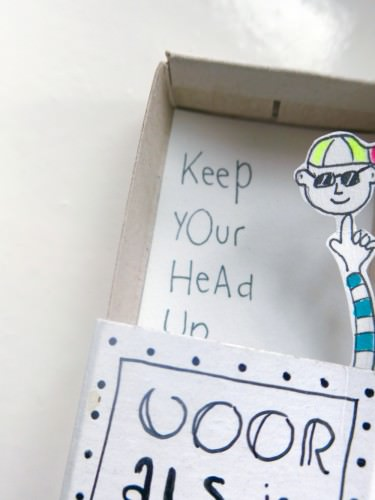 """Binnenkant van een designer luciferdoosje met de tekst """"keep your head up"""" met armpje met een hoofd erop"""""""